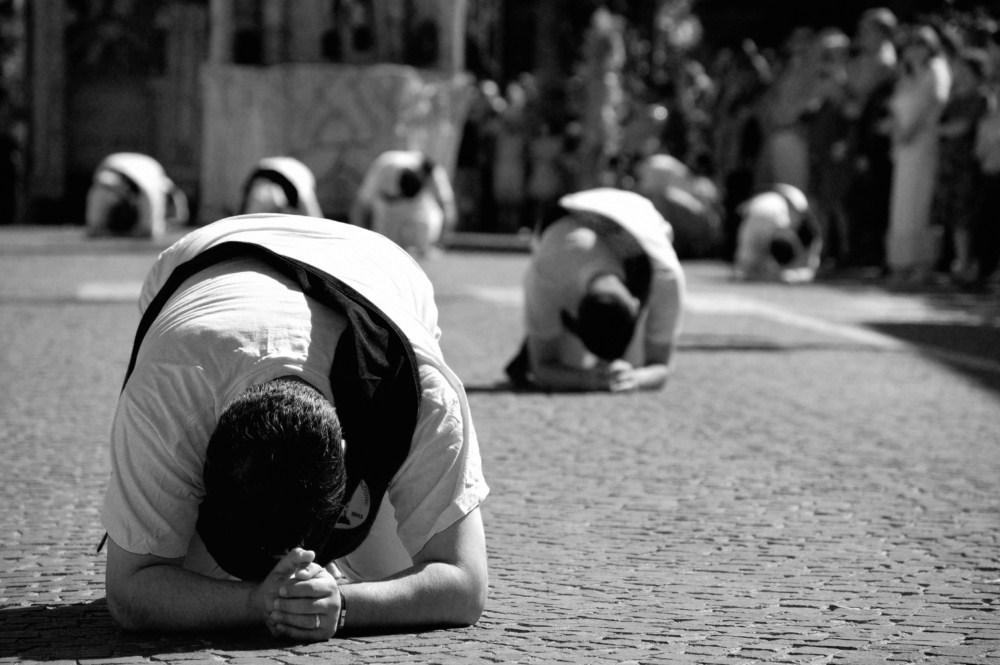 Prostrati ai suoi piedi - Momento particolarmente suggestivo della sfilata dei carri che avviene nella mattinata del 16 agosto; nei pressi della Chiesa di San Giovanni, nota anche come Chiesa di San Rocco, i Battenti si inginocchiano in segno di devozione al Santo.